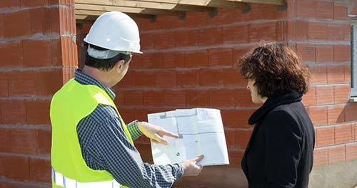 on construction site, man in hard hat with woman in suit looking at blueprints